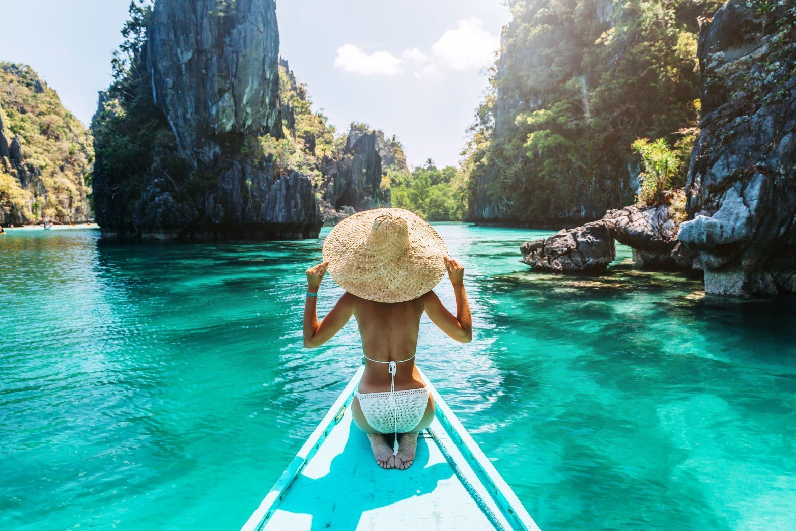 Lady-in-straw-hat-in-canoe-in-tropical-water